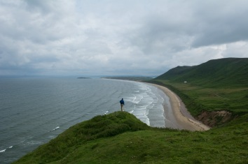 Tom waiting for the tides to drop so we could get to the crags at Rhossili Bay.